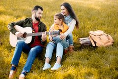 Family with daughter relaxing on a grassy hill while father playing. The guitar stock photography