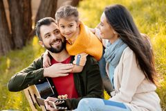Family with daughter relaxing on a grassy hill, while little girl. Hugging her father stock photo