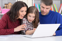 Family with a daughter using a laptop. Portrait of a family with a daughter using a laptop Royalty Free Stock Photos