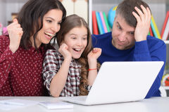Family with a daughter using a laptop. Portrait of a family with a daughter using a laptop Stock Images