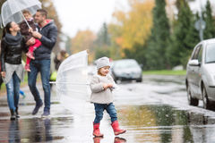 Family with daughters under the umbrellas. Walk on rainy day. Stock Photography