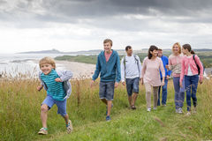 Family day at the beach. A family are walking on the sand dunes, they are all smiling and talking amounst themselves Royalty Free Stock Photo