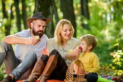 Family day concept. Happy family with kid boy relaxing while hiking in forest. Family weekend. Mother father and little. Son sit forest picnic. United with stock photo