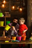 Family day. Greenhouse. bearded man and little boy child love nature. Flower care watering. Soil fertilizers. Father and stock image