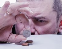 Family debts. Young frustrated and desperate man counting small Royalty Free Stock Photo