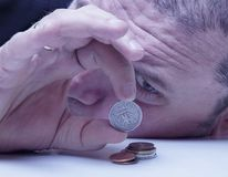 Family debts. Young frustrated and desperate man counting small Stock Photos