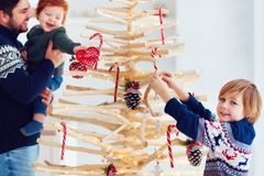 Family decorates an extraordinary christmas tree made of branches and driftwood at home stock photos