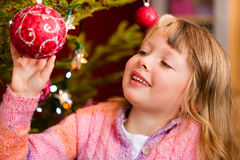 Family decorating Christmas tree. Young girl helping decorating the Christmas tree, holding some Christmas baubles in her hand Royalty Free Stock Photo