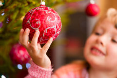 Family decorating Christmas tree. Young girl helping decorating the Christmas tree, holding some Christmas baubles in her hand Stock Images