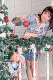 Family decorating a Christmas tree with boubles in the living-room Stock Photo