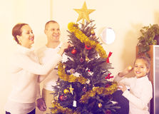 Family decorating Christmas tree. Family with daughter decorating Christmas tree in the living room at home. Focus on woman Royalty Free Stock Photography