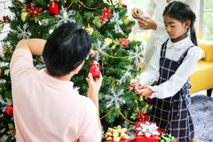 Family decorating a Christmas tree and Father giving Christmas G. Ift,Christmastime celebration and Happy new year royalty free stock image