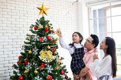 Family decorating a Christmas tree and Father giving Christmas G. Ift,Christmas celebration and Happy new year stock image