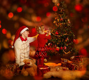 Family decorating Christmas tree. Father and kid celebrate Xmas. Family decorating Christmas tree. Father in santa hat and kid celebrate Xmas Royalty Free Stock Images