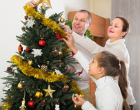 Family decorating Christmas tree. Happy parents and child decorating Christmas tree at living room. Focus on girl Stock Photos