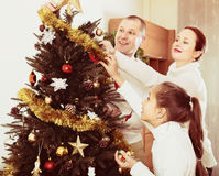 Family decorating Christmas tree. Happy parents and child decorating Christmas tree at living room. Focus on girl Royalty Free Stock Photo