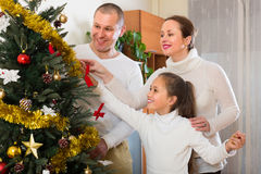 Family decorating Christmas tree. Happy parents and girl decorating Christmas tree in the living room at home Royalty Free Stock Image
