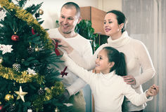 Family decorating Christmas tree. Happy parents and girl decorating Christmas tree in the living room at home Stock Photos