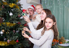 Family decorating Christmas tree at home. Cheerful family with kids decorating Christmas tree together at home. Focus on girl Royalty Free Stock Photo