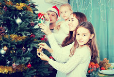 Family decorating Christmas tree at home. Cheerful family with kids decorating Christmas tree together at home. Focus on girl Royalty Free Stock Images