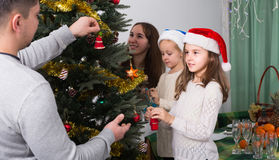 Family decorating Christmas tree at home. Cheerful parents with little daughters decorating Christmas tree together at home. Focus on girl Royalty Free Stock Photos