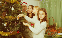 Family decorating Christmas tree at home. Cheerful parents and two little girls decorating Christmas tree together at home. Focus on girl Royalty Free Stock Images