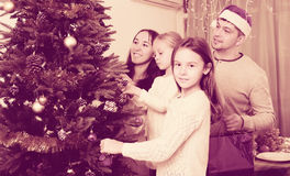 Family decorating Christmas tree at home. Cheerful family with two little daughters decorating Christmas tree together at home. Focus on girl Royalty Free Stock Photos
