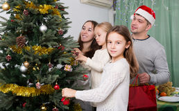 Family decorating Christmas tree at home. Cheerful family with two little daughters decorating Christmas tree together at home. Focus on girl Royalty Free Stock Images