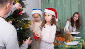Family decorating Christmas tree at home. Cheerful united family with kids decorating Christmas tree together at home. Focus on girl Stock Image