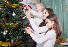 Family decorating Christmas tree at home. Cheerful united family with little daughters decorating Christmas tree together at home. Focus on girl Stock Photo