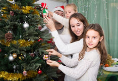 Family decorating Christmas tree at home. Cheerful young parents with two little daughters decorating Christmas tree at home. Focus on girl Royalty Free Stock Photo