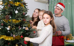 Family decorating Christmas tree at home. Cheerful young parents with two little daughters decorating Christmas tree and smiling. Focus on girl Stock Photography