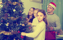 Family decorating Christmas tree at home. Cheerful young parents with two little daughters decorating Christmas tree and smiling. Focus on girl Royalty Free Stock Photography