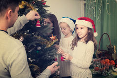Family decorating Christmas tree at home. Cheerful young parents and two little girls decorating Christmas tree together at home. Focus on girl Royalty Free Stock Photos