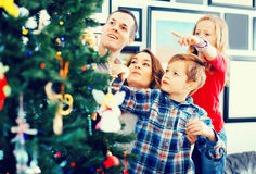 Family decorating Christmas tree at home. Happy cheerful family decorating Christmas tree at home Stock Image