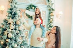 Happy family decorating a Christmas tree with boubles in the living-room. Family decorating a Christmas tree in home Stock Photo