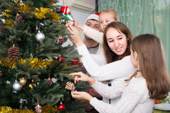 Family decorating Christmas tree at home. Happy smiling family with two little daughters decorating Christmas tree together at home. Focus on woman Royalty Free Stock Images