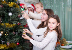 Family decorating Christmas tree at home. Happy family with two little daughters decorating Christmas tree together at home. Focus on girl Royalty Free Stock Photos