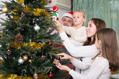 Family decorating Christmas tree at home. Happy young parents with two children decorating Christmas tree at home. Selective focus Stock Photo