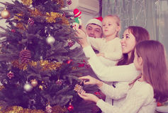 Family decorating Christmas tree at home. Happy young parents with two children decorating Christmas tree at home. Selective focus Royalty Free Stock Photography
