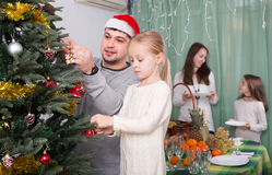Family decorating Christmas tree at home. Happy young parents with two children decorating Christmas tree and serving table for dinner at home. Focus on girl Royalty Free Stock Photography