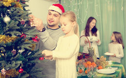 Family decorating Christmas tree at home. Happy young parents with two children decorating Christmas tree and serving table for dinner at home. Focus on girl Royalty Free Stock Images
