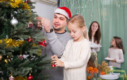 Family decorating Christmas tree at home. Joyful family with two little daughters decorating Christmas tree and serving table at home. Focus on girl Royalty Free Stock Images