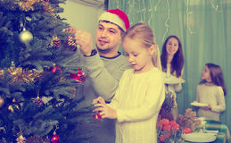 Family decorating Christmas tree at home. Joyful family with two little daughters decorating Christmas tree and serving table at home. Focus on girl Stock Photography