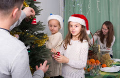 Family decorating Christmas tree at home. Two happy little daughters and their parents decorating Christmas tree at home. Focus on girl Royalty Free Stock Photo