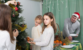 Family decorating Christmas tree at home. Young parents and two happy little daughters decorating Christmas tree at home and serving table. Focus on girl Royalty Free Stock Image