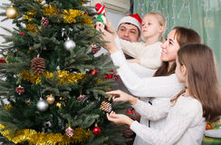 Family decorating Christmas tree at home. Young united family of four decorating Christmas tree together at home. Focus on woman Stock Photo