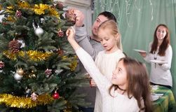 Family decorating Christmas tree at home. Young united family with kids decorating Christmas tree together at home. Focus on man Royalty Free Stock Photography