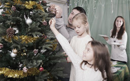 Family decorating Christmas tree at home. Young united family with kids decorating Christmas tree together at home. Focus on man Royalty Free Stock Image