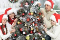 Family decorating Christmas tree stock photos